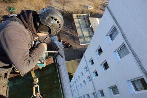Kletterer arbeitet am Dach