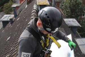 Industriekletterer beim zurechtschneiden einer Zinktafel für eine Kaminverkleidung