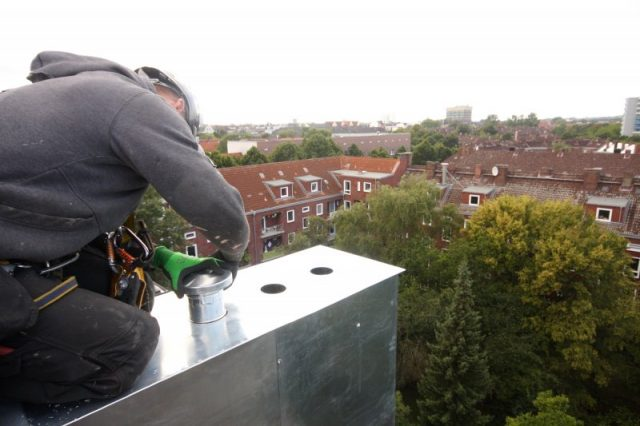 montage von Schornsteinverkleidung mit Zinkblech von Höhenarbeiter