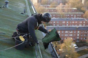 Höhenarbeiter säubert Dach