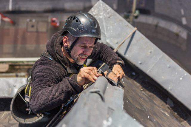 Dachkletterer befestigt Blech in Seilzugangstechnik
