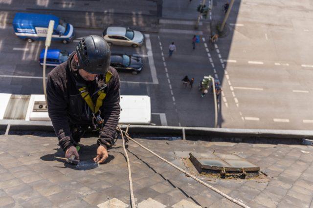 Höhenarbeiter passt schiefer in Dachfläche ein