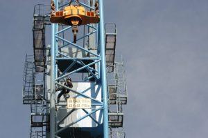 Kletterarbeiter klettert mit Seilen am Kran