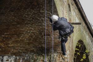 Kletterarbeiter kontrolliert Brückenpfeiler