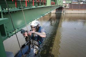 Industriekletterer an einer Brücke