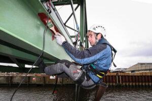 Kletterarbeiter bei Korrosionsschutzarbeiten