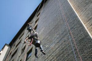 Kletterer beschichten eine Fassade