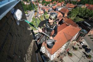 Höhenarbeiter beschichtet eine Fassade