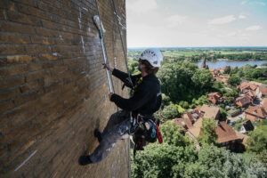 Kletterarbeiter beschichtet eine Hochhausfassade