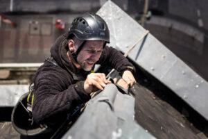 Kletterer passt Gratblech an was vom Sturm beschädigt wurde