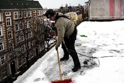 Höhenarbeiter entfernt Schnee vom Dach