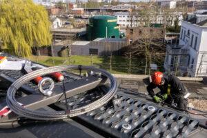 Industriekletterer montiert ein Rückhaltesystem auf ein Dach