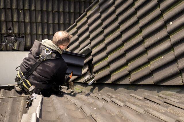 Dachdecker wechselt Dachziegel