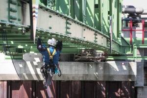 Höhenarbeiter klettert unter einer Brücke