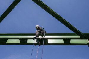 Industriekletterer sitzt auf einem Brückenträger