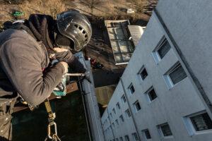 Industriekletterer sichert Dachpappe nach einem Sturm