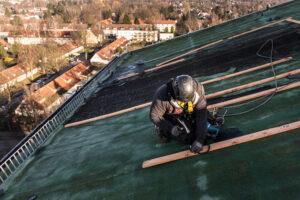 Kletternder Dachdecker bei der Arbeit