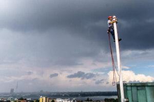 Industriekletterer klettert auf einen Fahnenmast