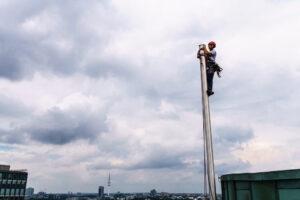Höhenarbeiter klettert in die Fahnenmastspitze
